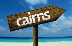 Photo of signpost to cairns from Sydney on a beach
