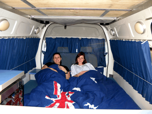 Photo of big double bed with two girls under the blankets inside this Automatic campervan hire