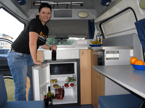 Inside the kitchen of this Automatic campervan for hire showing 80L fridge