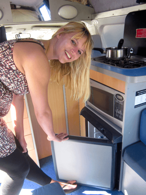 Lovely Sara using the 55L fridge inside the kitchen of this 3 Person Campervan Hire