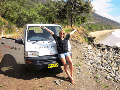 Campervan Rental Brisbane - lovely girl standing outside the campervan by the beach