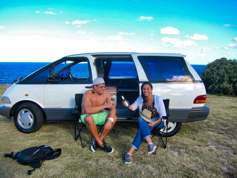 2 person campervan hire - two travellers enjoying a beer outside the campervan - cheers!