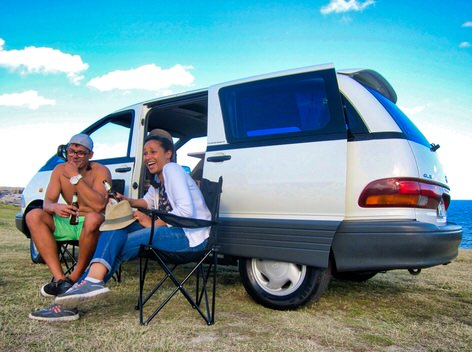 Two people drinking and having fun at the beach after hiring a campervan