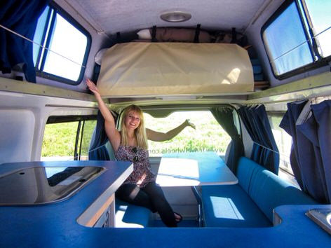 Sara inside the Lounge area of 3 Person Toyota Hiace Campervan
