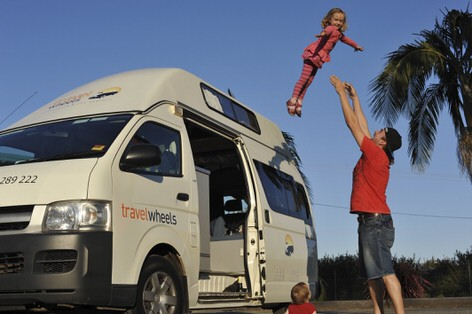 Family playing with kids outside their family friendly Toyota automatic campervan for sale